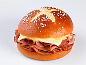 A pretzel roll filled with pastrami and cheese