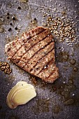 A grilled tuna steak with sesame seeds and slices of ginger