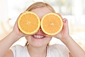 Young girl holding oranges over eyes