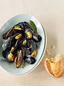 Steamed mussels with a chunk of baguette