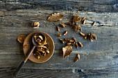 Bucheckern (Fagus sylvatica) in Löffel und Schälchen auf Holztisch
