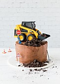 A chocolate cake topped with a digger and building site decorations