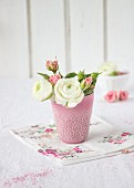 Ranunculus and roses in pink vase