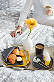 Croissants, eggs, coffee and yellow poppy on breakfast tray on bed with woman in background
