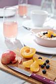 Holzbrett mit Pflaume und Heidelbeeren auf gedecktem Frühstückstisch
