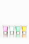 Different-coloured mouthwash in four shot glasses