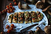 Vegan 'coca' (Spanish pizza) with wild mushrooms, tomatoes and onion