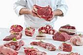 Koch präsentiert verschiedene frische Fleischsorten