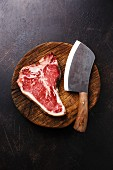 A raw dry-aged T-bone steak with a meat cleaver on a wooden board