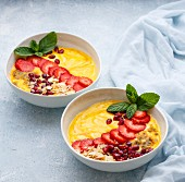 Mango and passion fruit smoothie bowls topped with strawberries and almonds