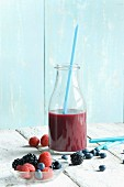 A blueberry smoothie with raspberries, blackberries and blueberries on the table next to it