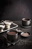 Tassen mit heißer Schokolade auf Holztisch