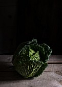 A savoy cabbage on a wooden surface