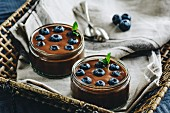 Chocolate pudding with blueberries in glass jars