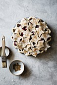 Unbaked cherry pie with shortcrust pastry stars and cinnamon sugar