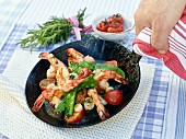 Prawns in a pan with sugar snap peas and cherry tomatoes
