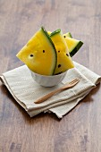 Pieces of yellow watermelon in a bowl on a napkin