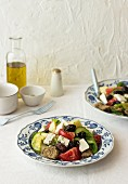 Tomato and cucumber salad with zucchini, potato, green pepper, black olives, oregano and farmhouse bread (Crete)