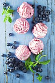 Blueberry ice cream and fresh blueberries on a blue background