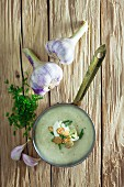Garlic soup in a saucepan on a wooden background
