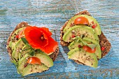 Wholegrain bread topped with avocado slices, tomato and a poppy