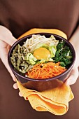 A person holding a bowl of bibimbap (rice dish from Korea)