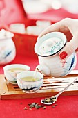 A woman pouring green tea from a teapot into Asian-style teacups (Asia)