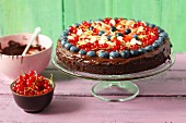 A sweet potato brownie cake with berries and flaked almonds