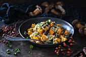 Vegan rice dish in a pan with pumpkin and wild mushrooms
