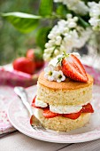 A mini Victoria sponge cake with strawberries and cream