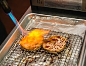 Pork with soy sauce being flame grilled with a gas burner (Japan)