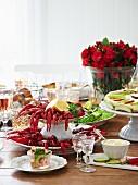 Gedeckter Tisch mit Flusskrebsen, Croissants, Apfeltorte, Mayonnaise und Meerrettichschnaps (Schweden)