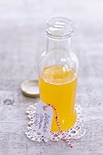 Woodruff and orange cordial in a small glass bottle with a cardboard tag