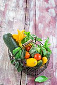Fresh summer vegetables and basil in a wire basket