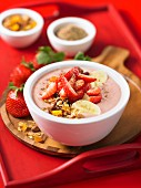 A strawberry smoothie bowl with banana and nuts