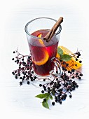 A glass of fruit tea with orange and a cinnamon stick
