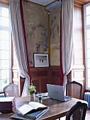 Holztisch im Salon mit Wandvertäfelung und Wandmalerei
