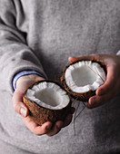 A person holding a coconut