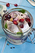 Marinated herring fillets with cranberries and raisins in a jar