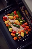 Chicken legs with vegetables on a baking tray