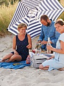 Three people having a picnic at the beach