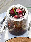 Black lentil salad with cherries in a glass jar