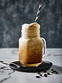 An espresso soda float in a glass with a straw