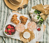 Rosé wine, strawberries, croissants, brie, a straw hat and a bouquet of flowers on a picnic blanket