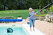 Woman cleaning her swimming pool