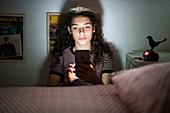 Teenage girl using a smartphone at night