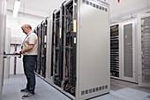 Technician checking servers in data centre