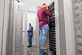 Technicians checking servers in data centre