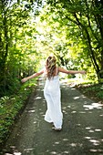 Woman in long white dress on country lane