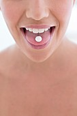 Woman with pill on tongue